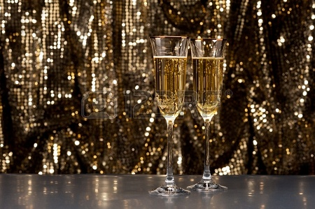 17234545-champagne-glasses-in-front-of-gold-glitter-background